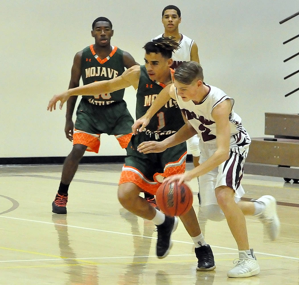 Horace Langford Jr./Pahrump Valley Times Junior guard Grant Odegard works his way past Mojave's DeSaun Smith during Tuesday night's Sunset League game in Pahrump.