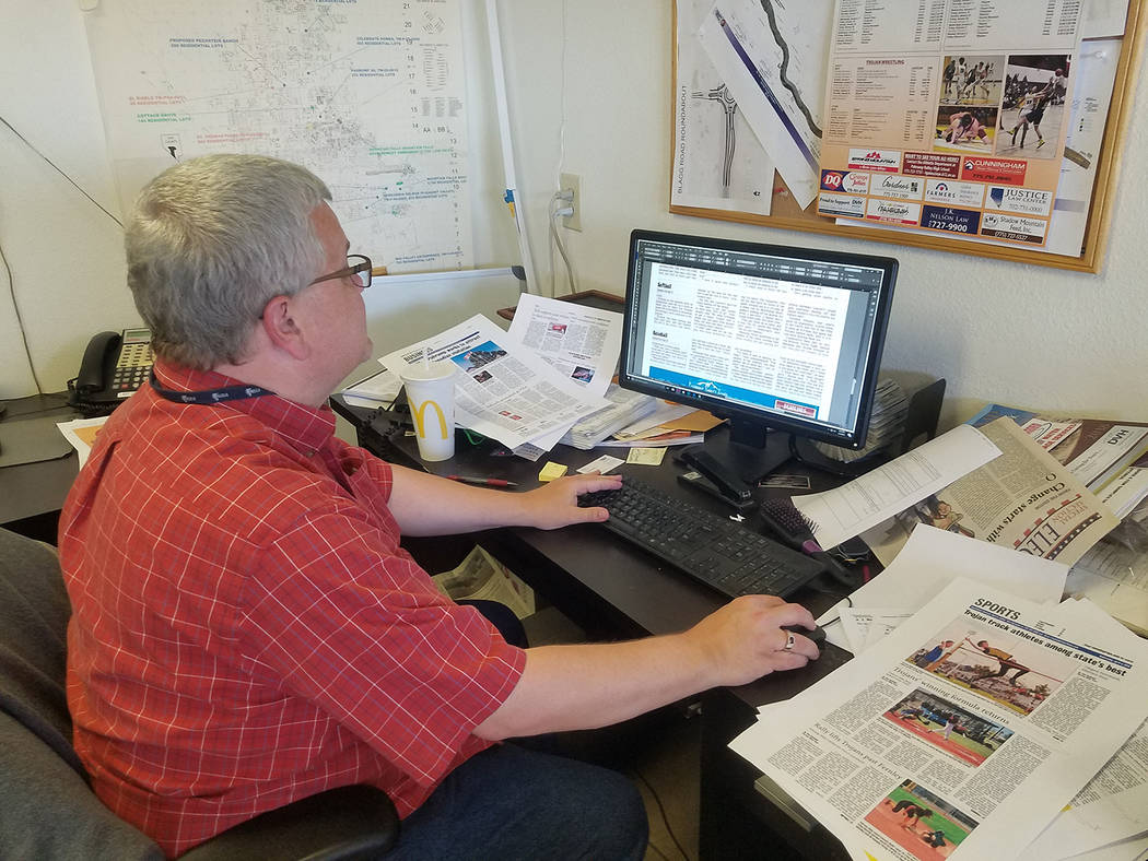 David Jacobs/Pahrump Valley Times Sports editor Tom Rysinski in the office making cuts and corrections before pages are sent to be printed. Full disclosure, that's not his desk.