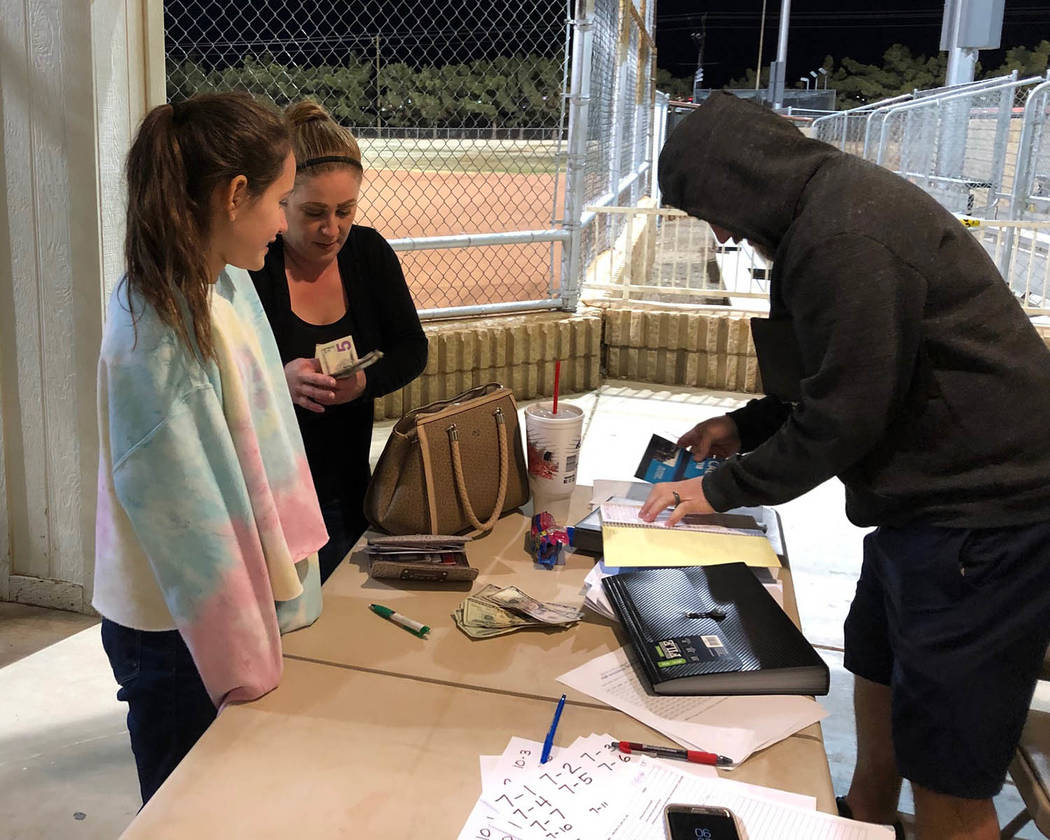 Tom Rysinski/Pahrump Valley Times Kayleen Carranza, left, braves the February cold to sign up for Pahrump Valley Little League softball Wednesday at Ian Deutch Memorial Park.