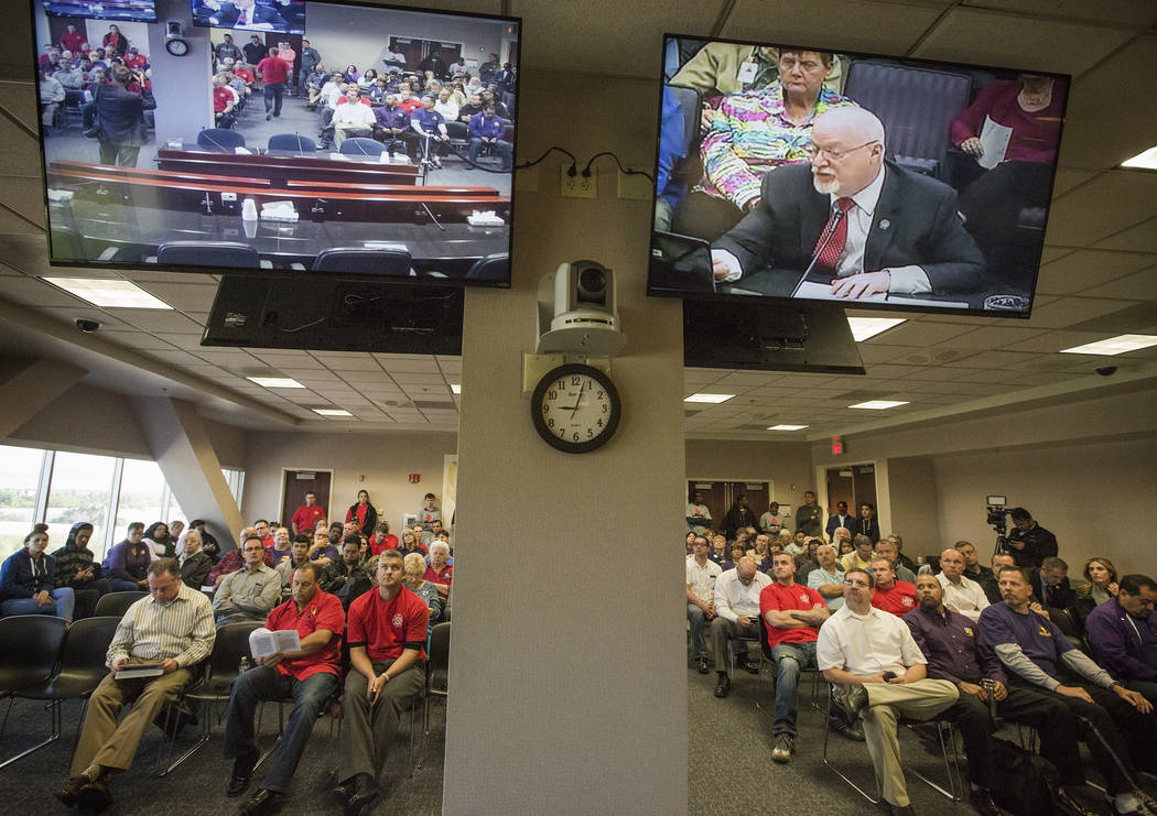 People listen while Assemblyman Randy Kirner, R-Reno, right on monitor, speaks during the Assembly Ways and Means Committee telecast hearing on AB190 Wednesday, April 15, 2015, at the Sawyer Build ...