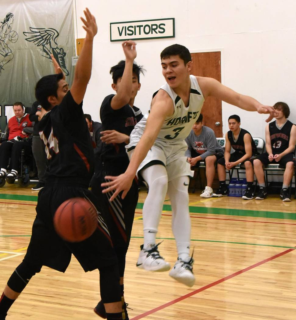 Richard Stephens/Special to the Pahrump Valley Times Beatty senior Alan Sandoval dishes under the basket Friday night against Sandy Valley. The Hornets defeated the Sidewinders 65-55 to clinch a r ...