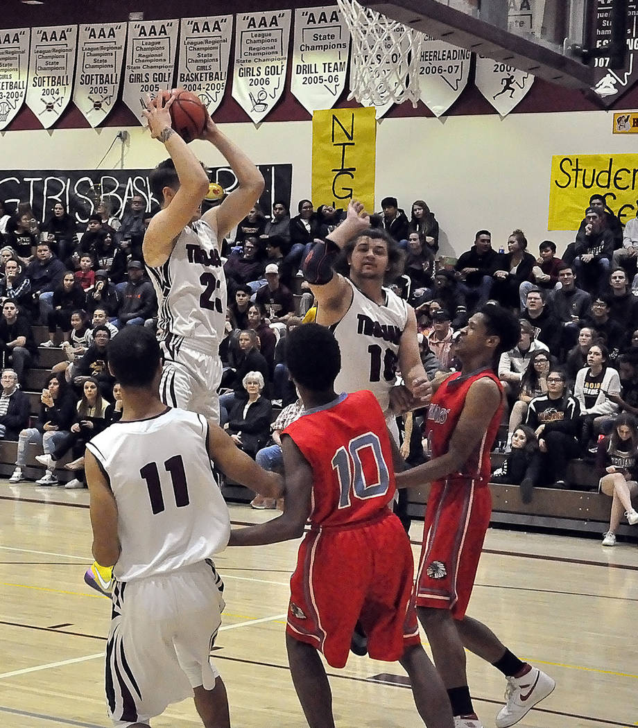 Horace Langford Jr./Pahrump Valley Times Senior forward Brayden Severt grabs a rebound against Western with Ethan Whittle, left, and Eric Toomer, right in on the play during Pahrump Valley's 54-50 ...