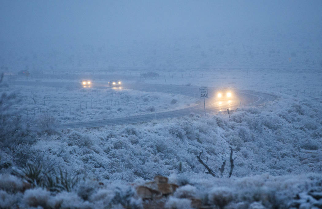 Vehicles drive along state Route 159 as snow falls around the Red Rock Canyon National Conservation Area outside of Las Vegas on Wednesday, Feb. 20, 2019. (Chase Stevens/Las Vegas Review-Journal) ...
