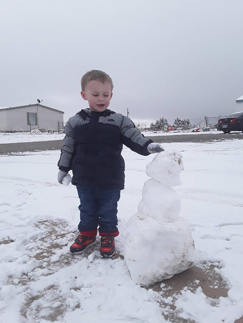 Selwyn Harris/Pahrump Valley Times Taylor Blankenship, 2, admires a snowman he and his father Tyler Blankenship created from Thursday's snowfall on the south end of the Pahrump Valley. The Nationa ...