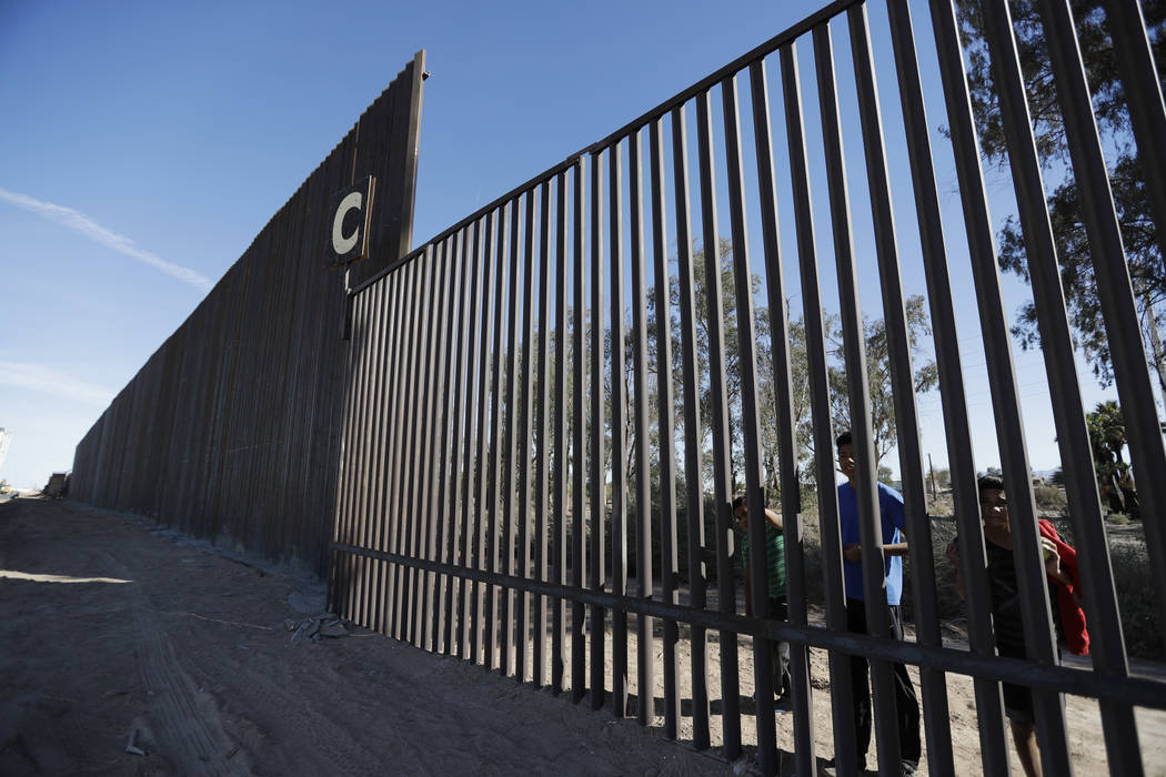 FILE - In this March 5, 2018, file photo, boys look through an older section of the border structure from Mexicali, Mexico, alongside a newly-constructed, taller section, left, in Calexico, Calif. ...