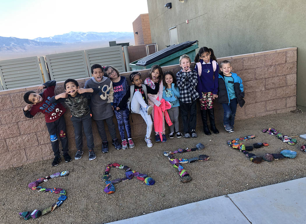 Special to the Pahrump Valley Times Local elementary school students enrolled in the school district's SAFE program, strike poses before colorful rocks painted during a recent parent engagement ni ...