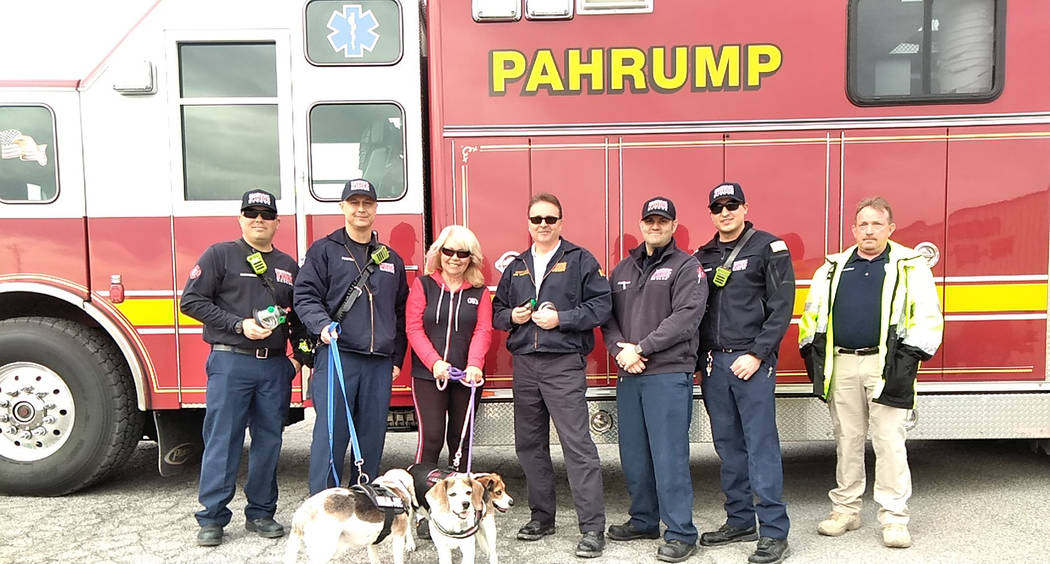 Selwyn Harris/Pahrump Valley Times Giselle Galassi holding her three Beagles stands alongside Pahrump Fire Chief Scott Lewis at her immediate left, following a donation of pet oxygen masks late la ...