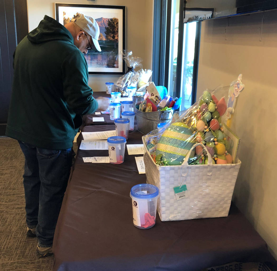 Tom Rysinski/Pahrump Valley Times Raffle prizes are inspected Saturday at Mountain Falls Golf Club after the golf was over at the No To Abuse Golf Tournament in Pahrump.