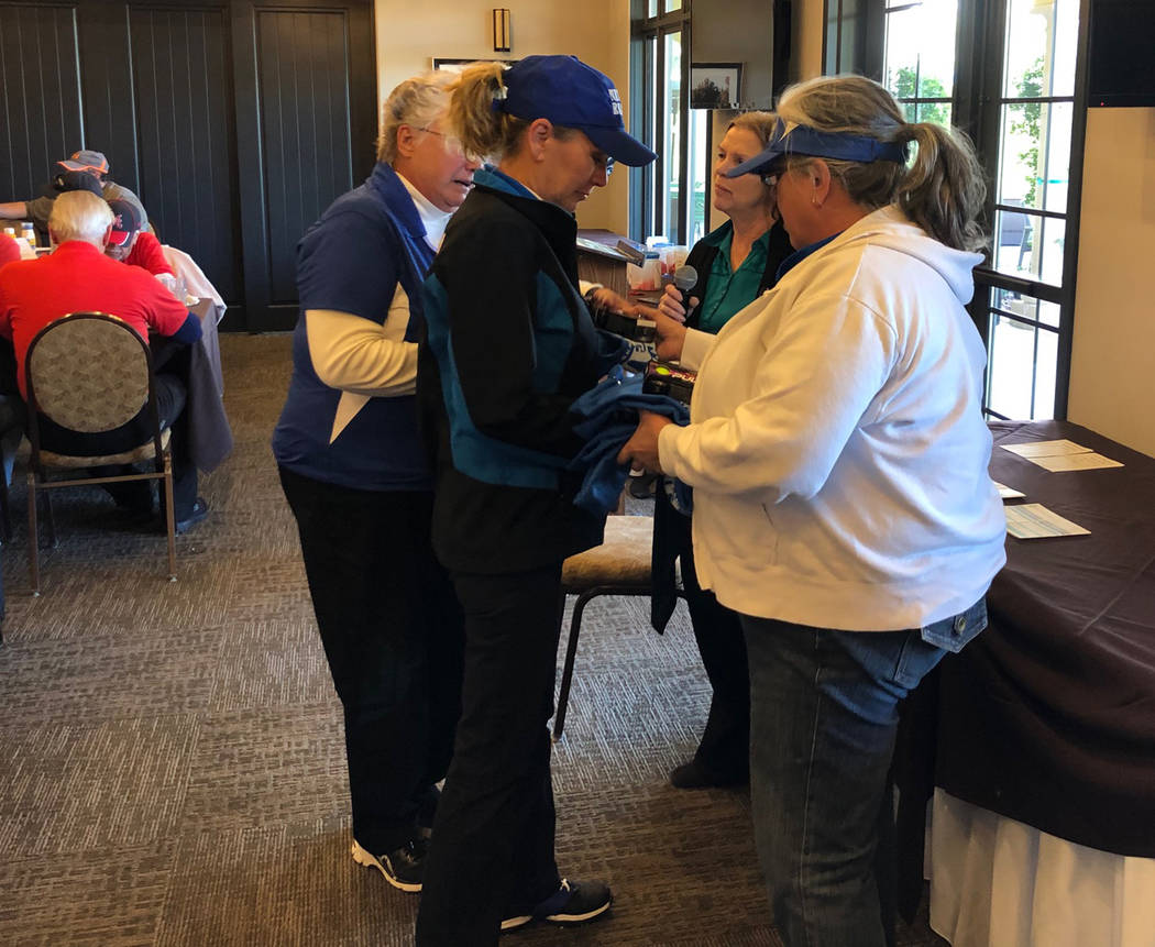 Tom Rysinski/Pahrump Valley Times Salli Kerr, second from right, gives members of the Nevada Realty women's foursome their prizes for finishing last at the No To Abuse Golf Tournament on Saturday ...
