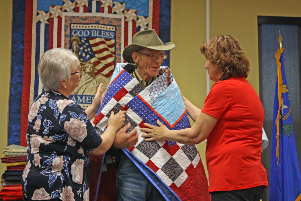 Robin Hebrock/Pahrump Valley Times Ladies of the Nye County Valor Quilters drape a Quilt of Valor around Army veteran Paul Riley.