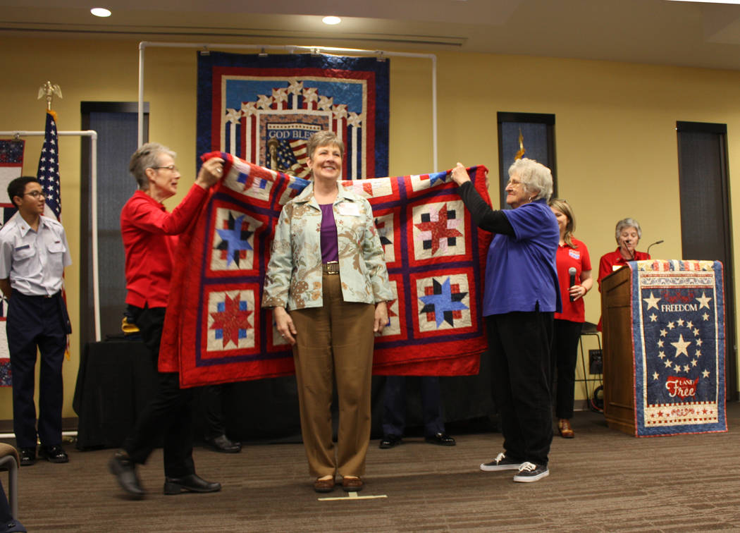 Robin Hebrock/Pahrump Valley Times U.S. Marine Corps veteran Laurie Wilson beams happily as she stands before her brand new Quilt of Valor.