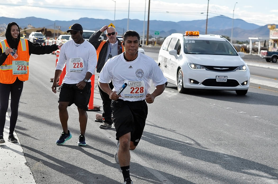 Horace Langford Jr./Pahrump Valley Times The South Gate, California, Police Department team transfers the baton at a checkpoint in Pahrump during last year's Baker to Vegas Challenge Cup Relay.