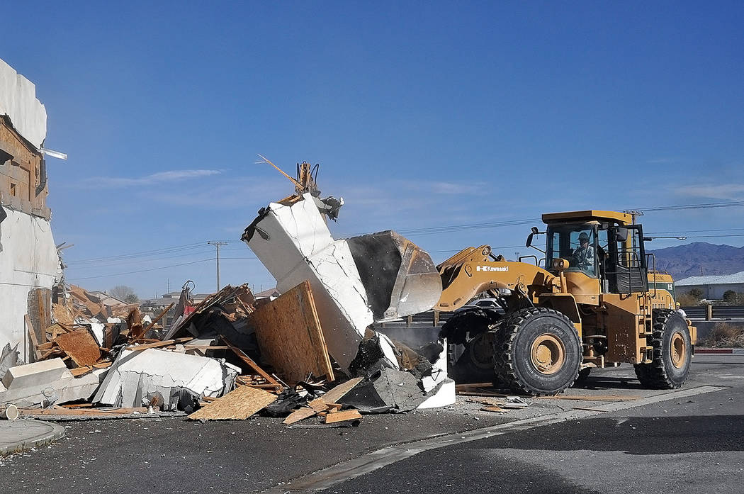 Horace Langford Jr./Pahrump Valley Times A bulldozer clears strewn debris from the former Kingdom Gentlemen's Club. Pahrump's Full-Throttle Excavation company was tasked with leveling the structu ...