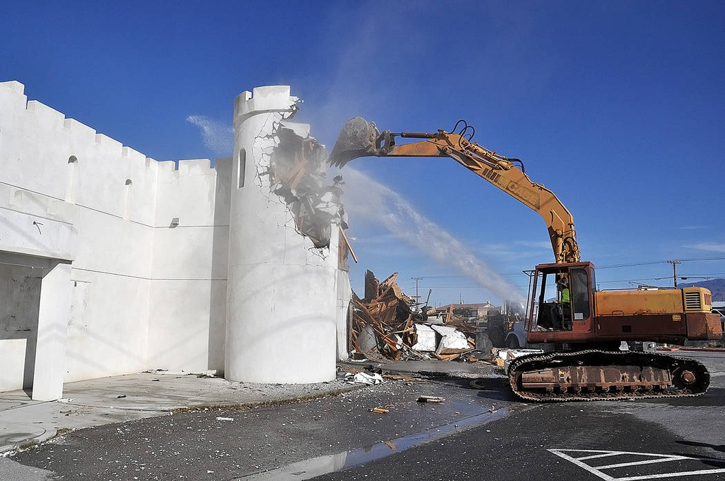 Horace Langford Jr./Pahrump Valley Times The bucket of an excavator takes down a raised section of the castle-themed Kingdom Gentlemen's Club at Homestead Road and Highway 160 on Friday March 15. ...