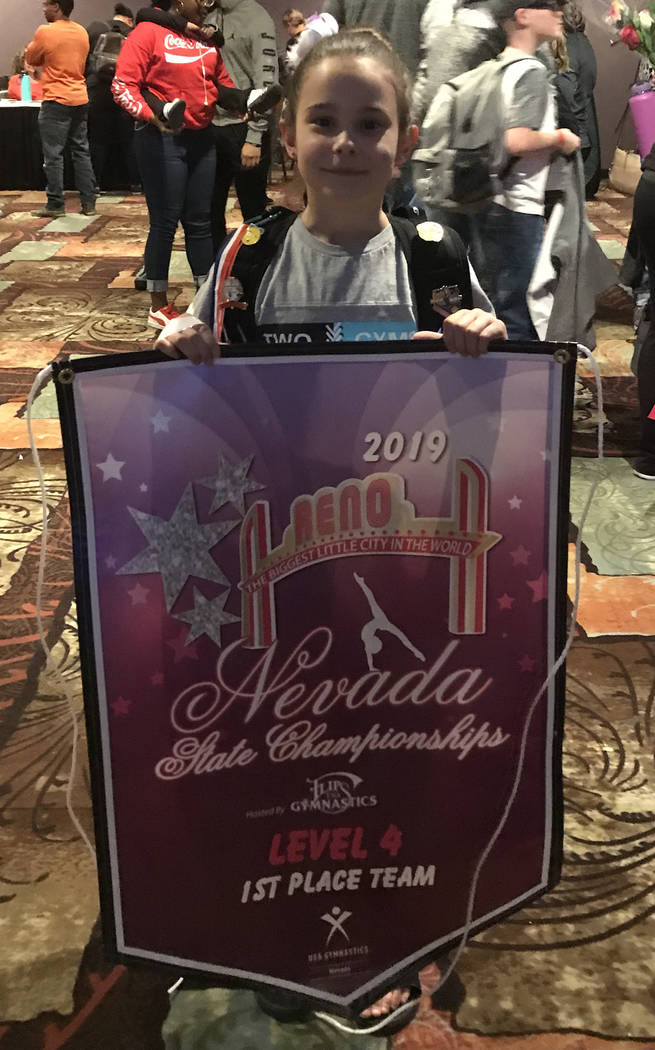 Melissa Plant/Special to the Pahrump Valley Times Arianna Plant holds the banner her Gymcats team earned for finishing in first place at the Nevada State Gymnastics Championships last weekend in Reno.