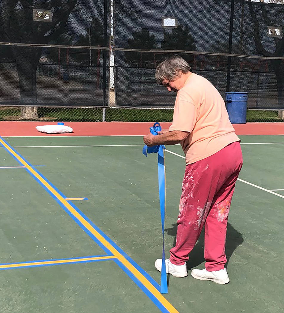 Tom Rysinski/Pahrump Valley Times Linda Delamare pulls up tape after pickleball lines were pain ...