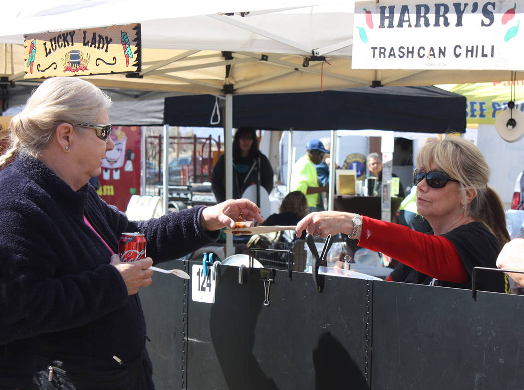 Robin Hebrock/Pahrump Valley Times Lynn Robinson of Lucky Lady hands over a sampling of her chili concoction to an eager taster.