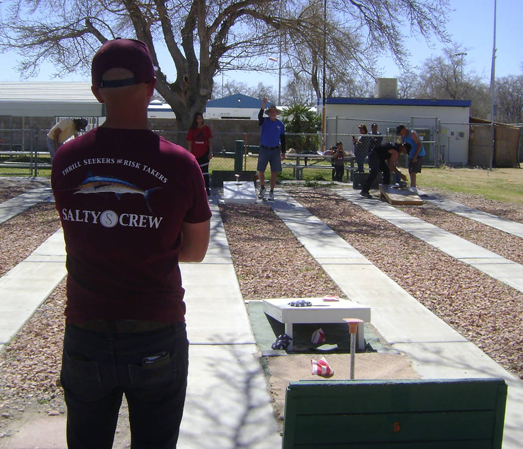 Mike Norton/Special to the Pahrump Valley Times Eric Barefield, left, watches as Don Brown takes his turn during Saturday's cornhole tournament at Petrack Park.
