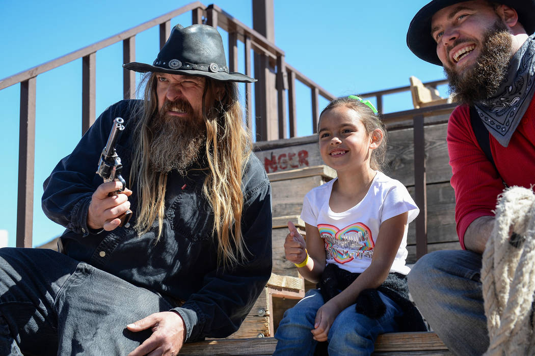Ellie Mendoza, 7, from Las Vegas, middle, poses for a photograph with Jesse Reeder, left, and Mike Kelly during the last day of operations at Bonnie Springs Ranch in Las Vegas, Sunday, March 17, 2 ...