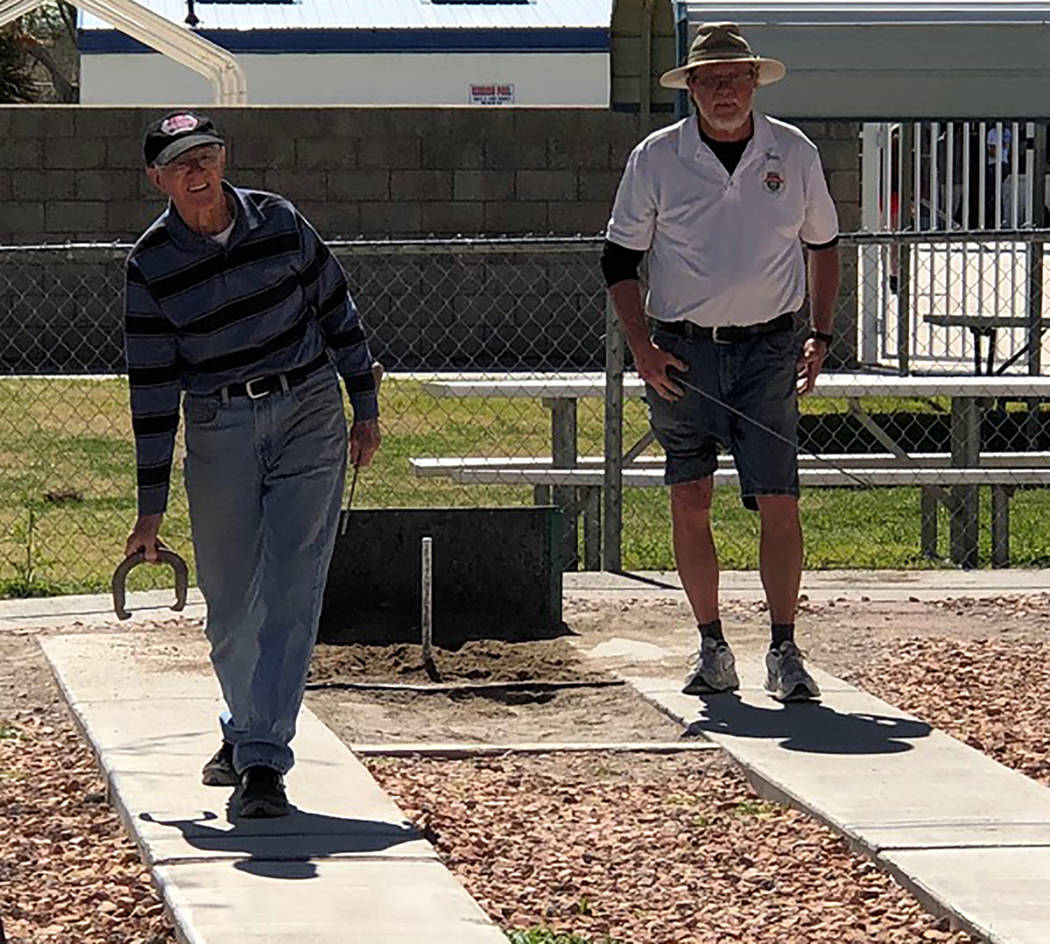 Tom Rysinski/Pahrump Valley Times Fred Kennedy, left, pitches as Don Brown waits his turn during a B Division game at the Pahrump Spring Open horseshoes tournament Saturday, March 23 at Petrack Park.