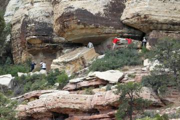 Archaeologists and volunteers work Thursday, May 19, 2011, to restore an ancient rock art site ...