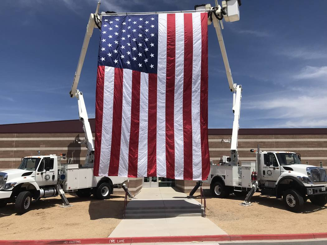 Jeffrey Meehan/Pahrump Valley Times A large American flag blows in the wind between two trucks ...