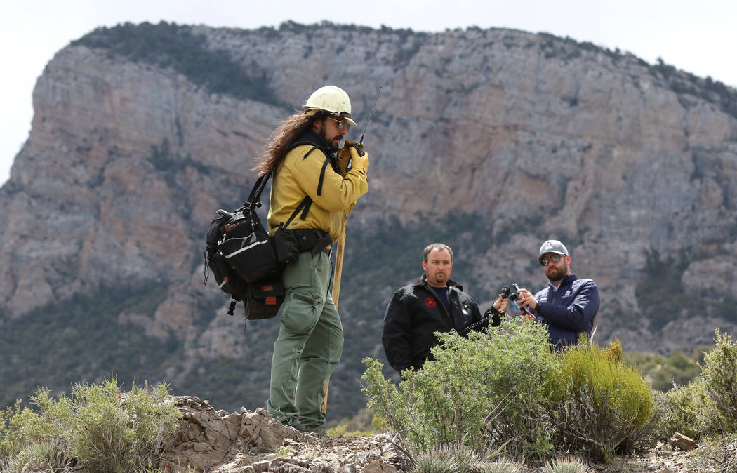 Andrew Merriam, squad leader and firefighter at Bureau of Land Management, radios as he conduct ...