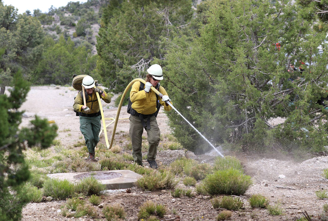 Firefighter from Bureau of Land Management Calvin Goff, front, and Travis Flowers spray water a ...