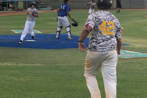 Tom Rysinski/Pahrump Valley Times Pahrump's James Metscher scores a run as Fidel Betancourt rac ...