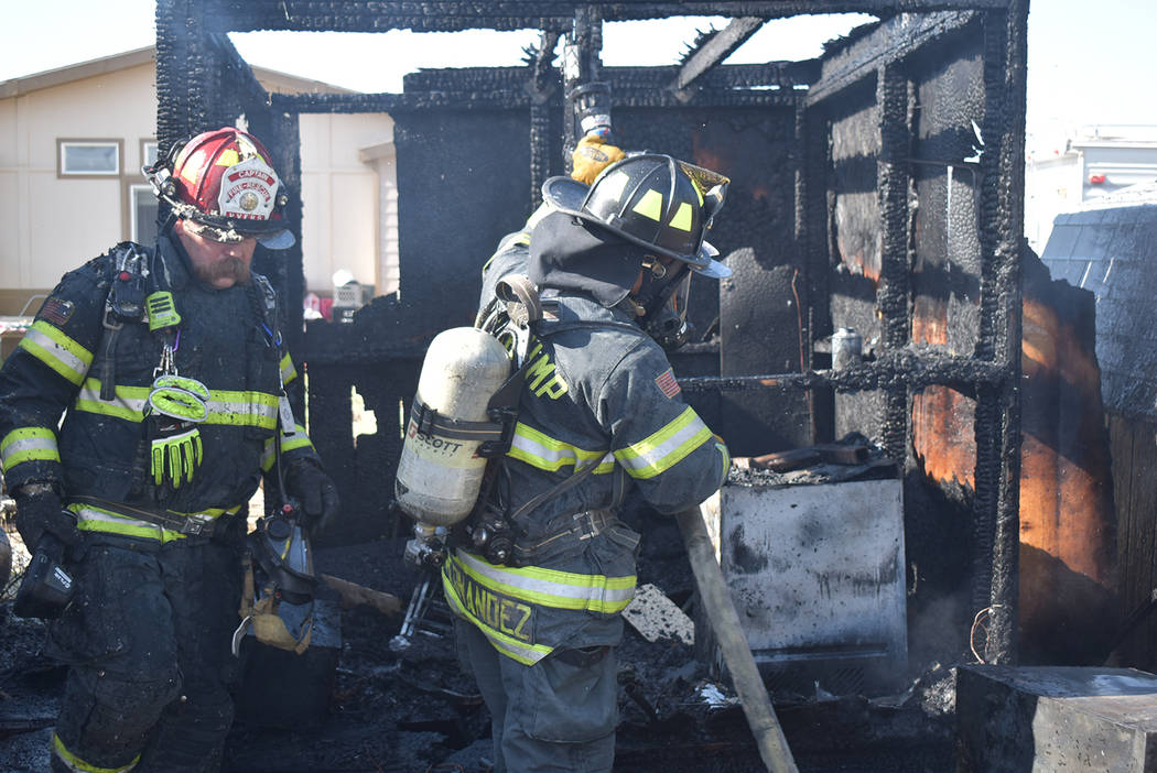 Special to the Pahrump Valley Times Pahrump firefighters inspect the remains of two sheds destr ...