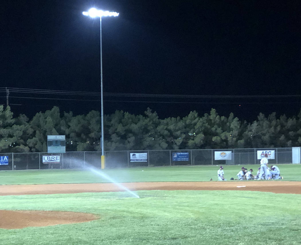 Tom Rysinski/Pahrump Valley Times Pahrump players take an impromptu break as the sprinklers com ...