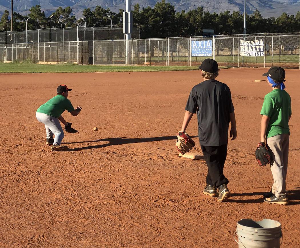 Tom Rysinski/Pahrump Valley Times Sergio Gonzalez fields a ground ball while his teammates wait ...