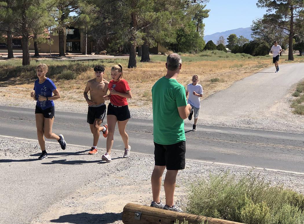 Tom Rysinski/Pahrump Valley Times Runners cross a road during a training run as Pahrump Valley ...