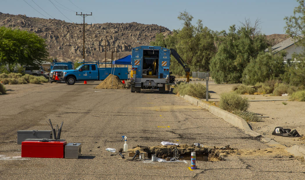 L.E. Baskow/Las Vegas Review-Journal An open hole revealing a broken gas line is repaired by a ...