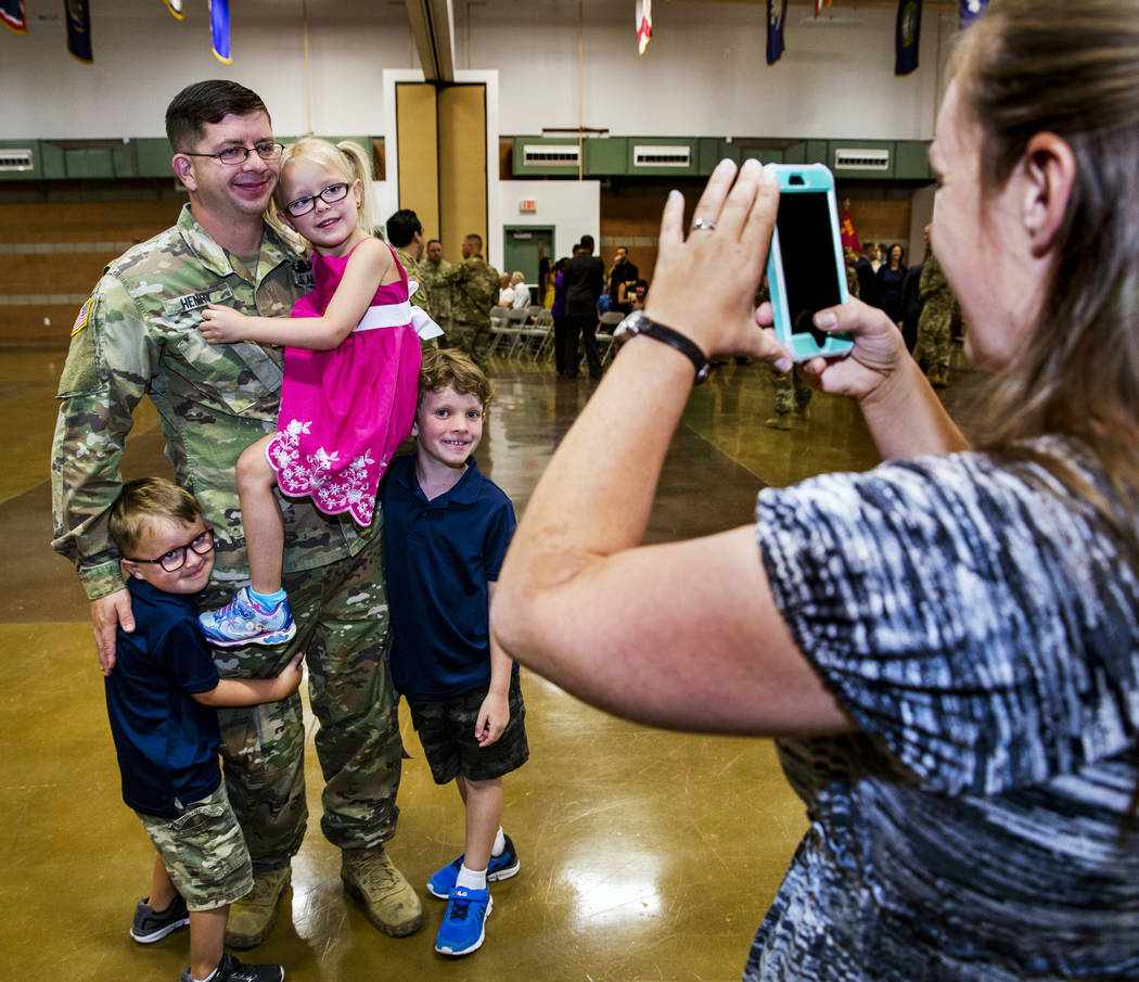 1st Lieutenant David Henry holds his daughter Karagan, 5, with son's Carrick, 5, left, and Owei ...
