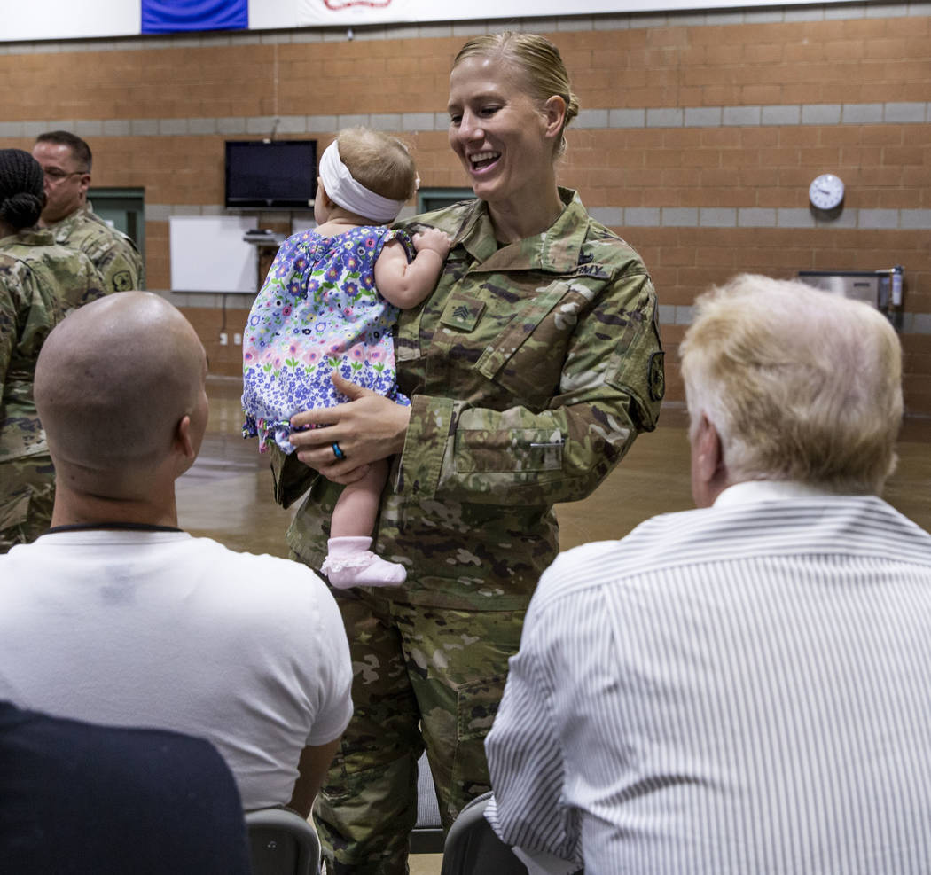 Sgt. Jessica Done holds her daughter Rylie, 8-month-old, as she talks with family before a mobi ...