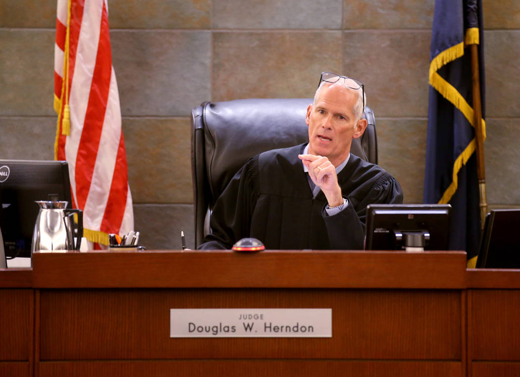 District Judge Douglas Herndon presides during the initial arraignment of some of the 23 people ...
