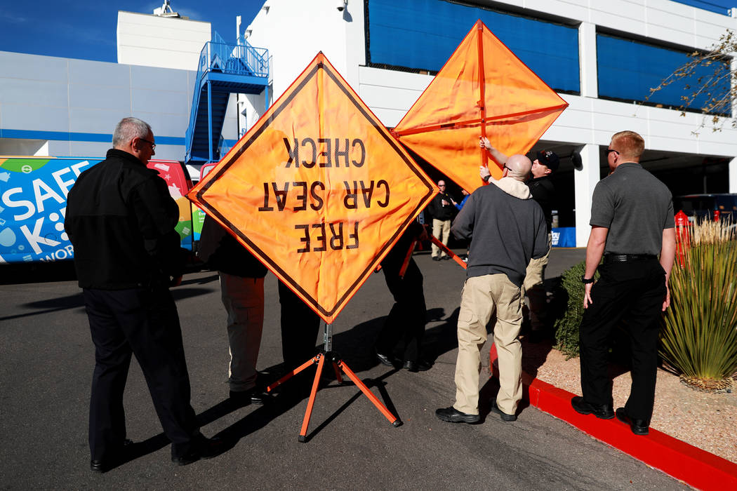 Nevada Highway Patrol troopers assemble a couple of signs to place on the corner of the car lot ...