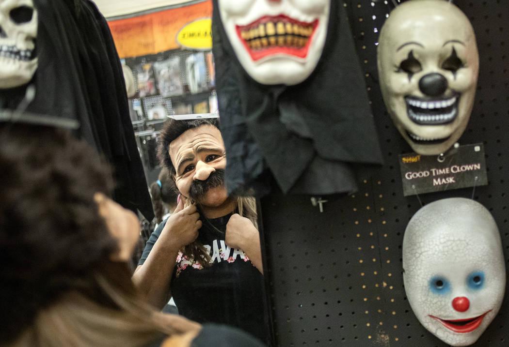 Ellen Schmidt/Las Vegas Review-Journal Laura Silva of St. George, Utah tries on a mask for her ...