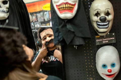 Ellen Schmidt/Las Vegas Review-Journal Laura Silva of St. George, Utah tries on a mask for her ...