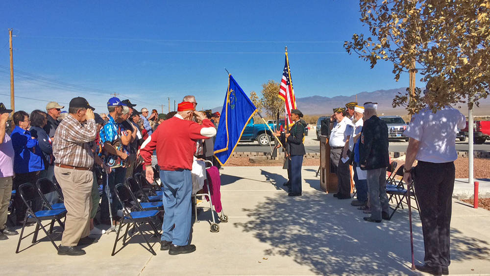 Robin Hebrock/Pahrump Valley Times A large crowd of attendees salute the flag as the Veterans o ...