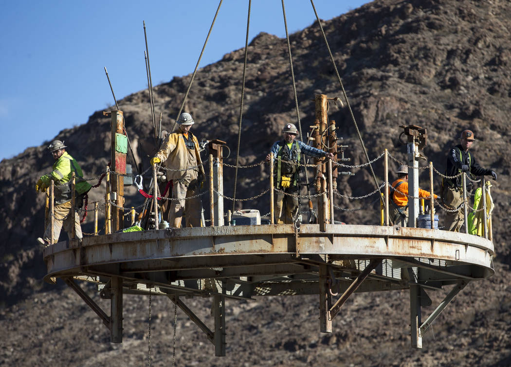 Workers prepare to be lowered down the access shaft for Southern Nevada Water Authority's low-l ...