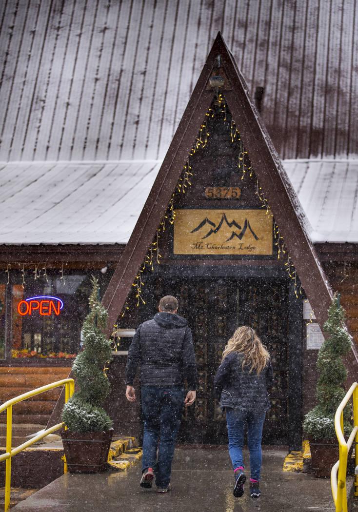 A couple walks through snow outside Mt. Charleston Lodge on Wednesday, Nov. 20, 2019. (L.E. Bas ...