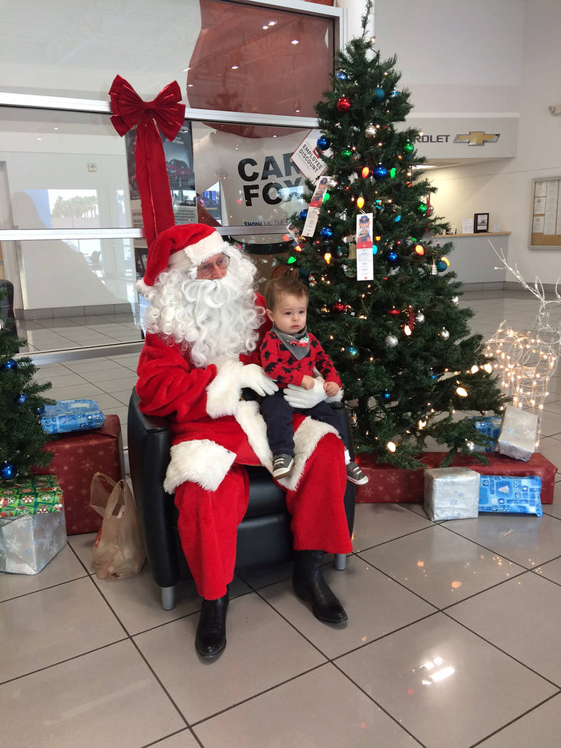 Robin Hebrock/Pahrump Valley Times Santa Claus poses with a tiny tot at the Pahrump Valley Lion ...