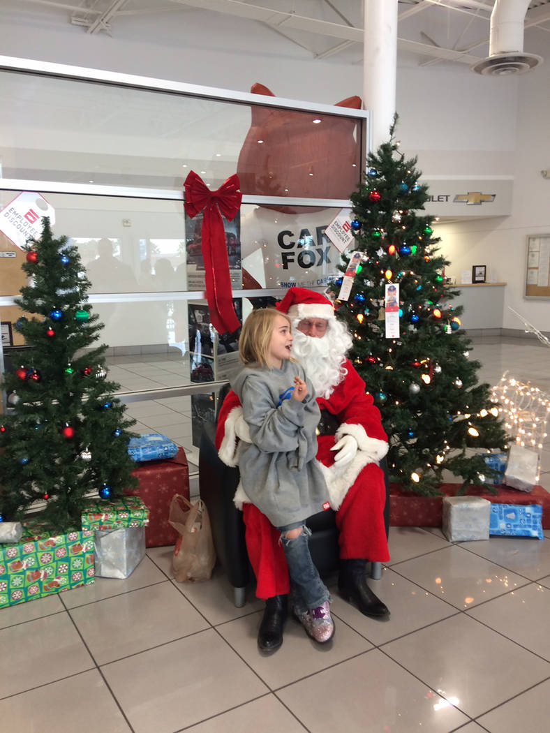 Robin Hebrock/Pahrump Valley Times A valley child sits down on Santa's lap and imparts her Chri ...