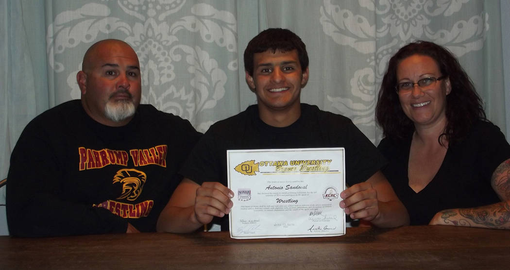 Pahrump Valley Times file photo Flanked by his parents, Antonio Sandoval displays his National ...