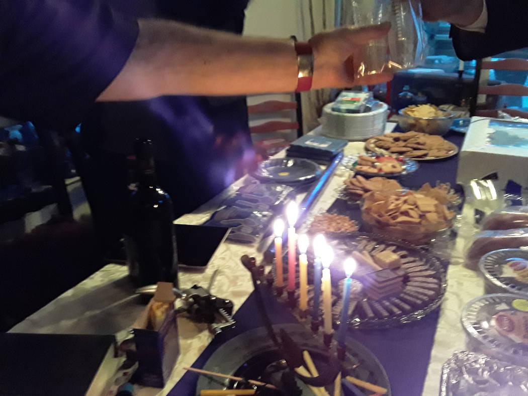 Selwyn Harris/Pahrump Valley Times Marty Greenfield prepares to break bread as a menorah glows ...