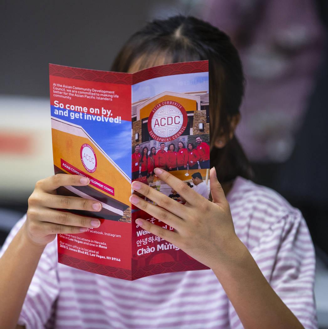 L.E. Baskow/Las Vegas Review-Journal Attendee Irene Cho reads an Asian Community Development Co ...