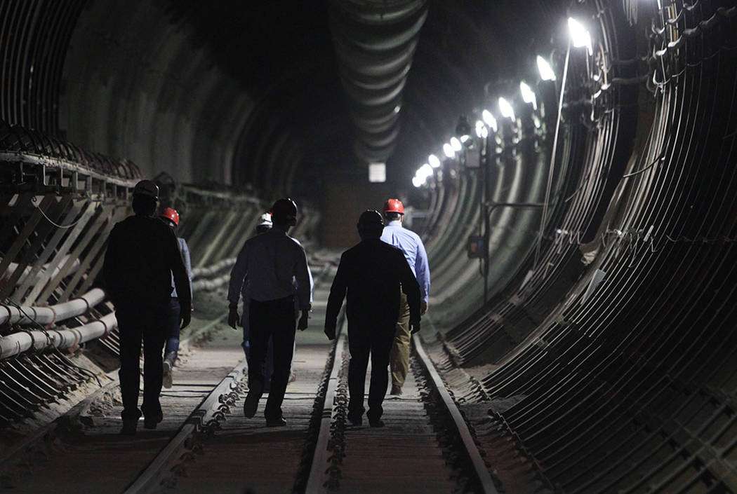 Department of Energy employees and members of the media walk toward the south portal entrance d ...