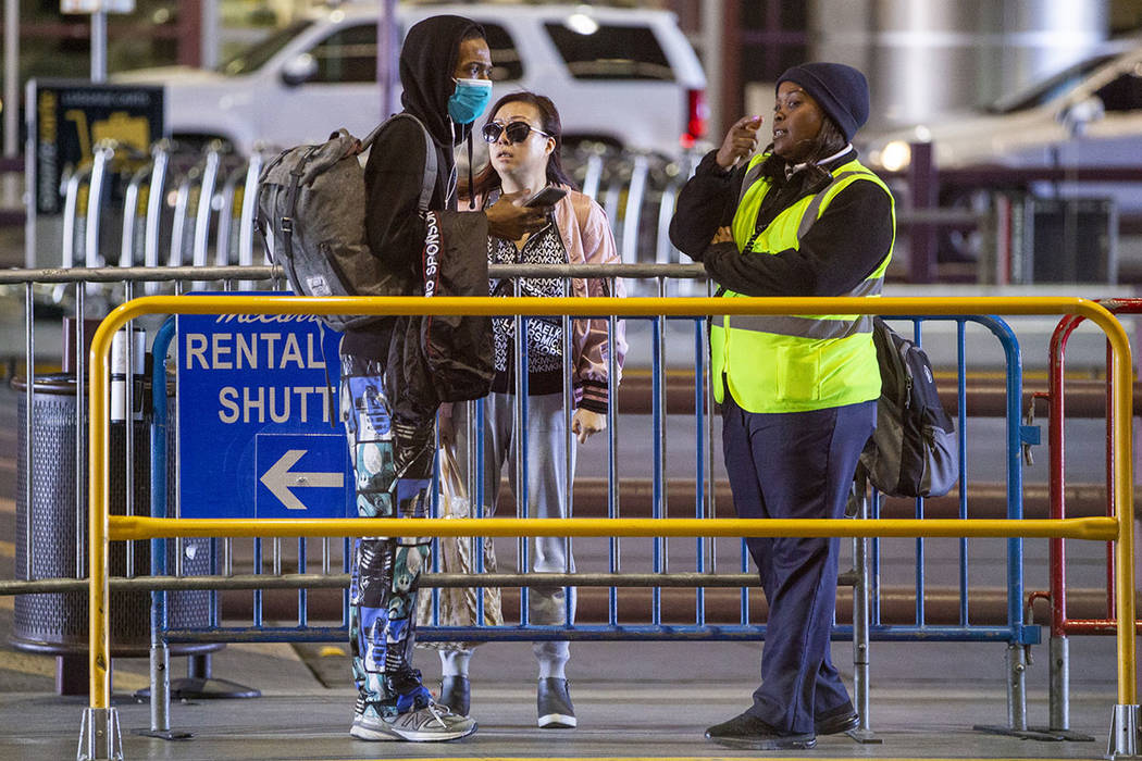 A passenger wears a face mask while asking for directions outside the Terminal 1 baggage claim ...